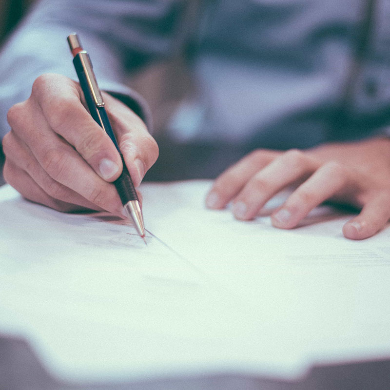 man filling out a form with a pen